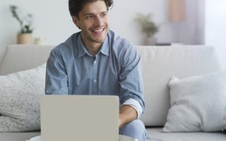 Smiling Man Using Laptop Making Video Call Sitting On Couch At Home. Free Space For Text